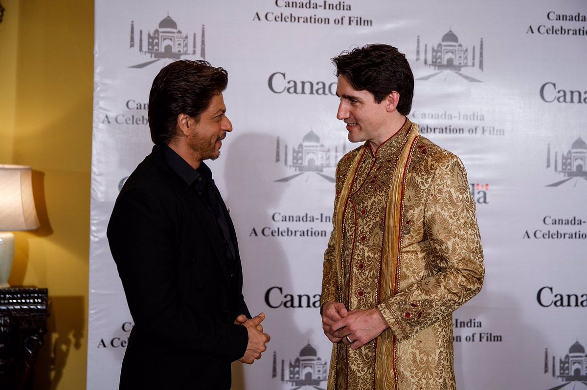Shah Rukh Khan greets Justin Trudeau, who glistens in gold.