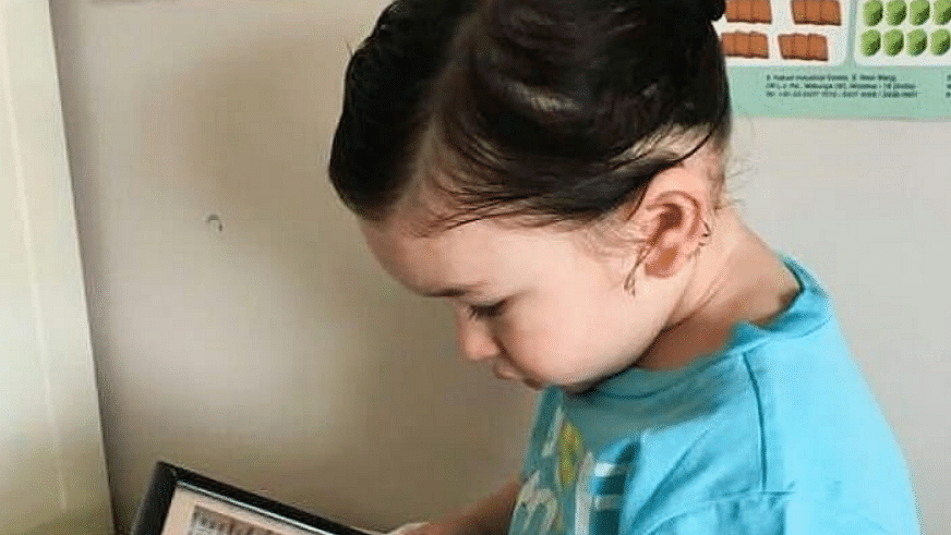 Taimur Ali Khan stares into a picture of his dad, Saif Ali Khan.