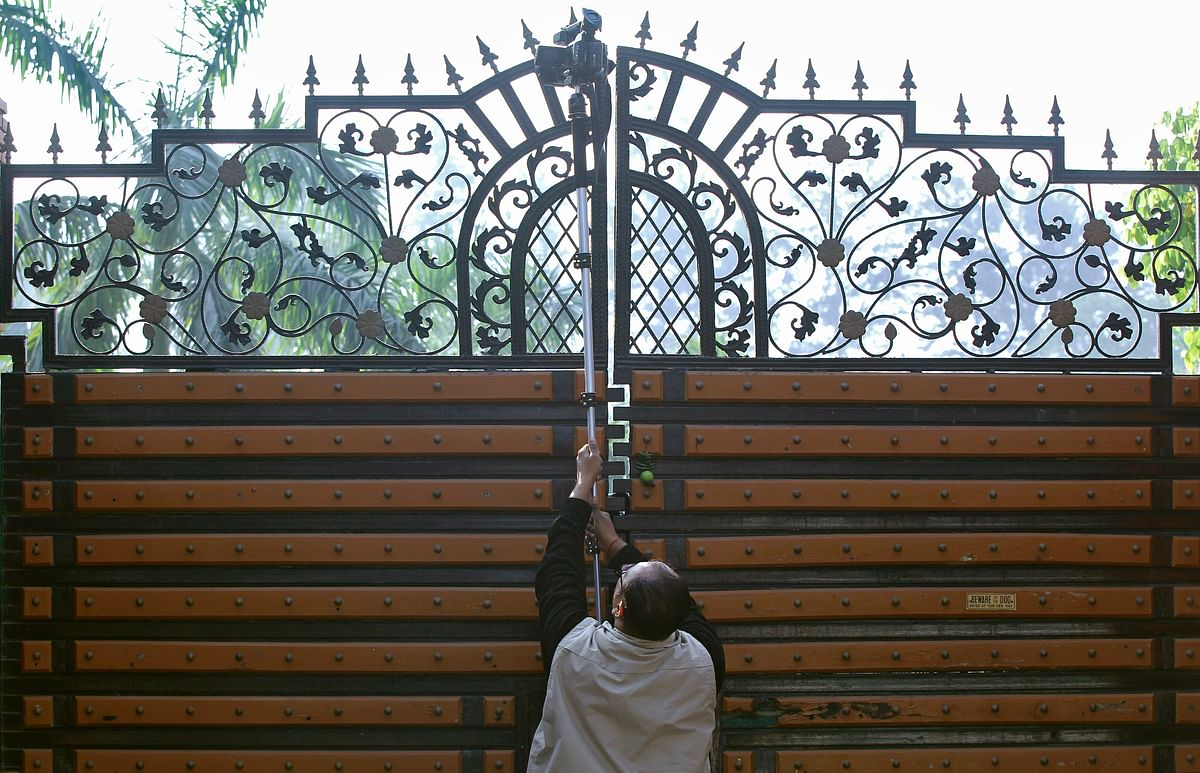 A news cameraman holds his camera aloft to film an inside view of corporate lobbyist Nira Radia's house in New Delhi, 21 December 2010.