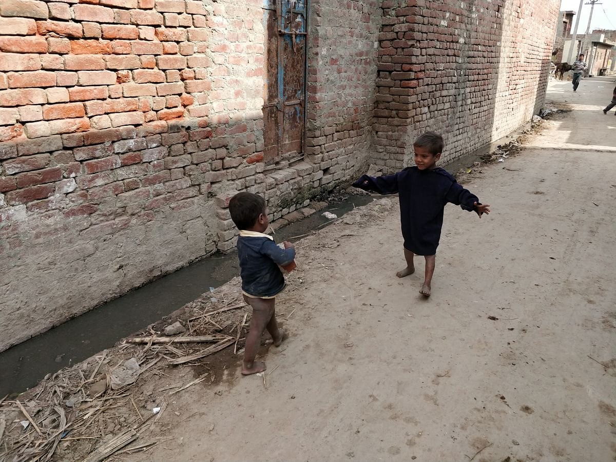 Dirty, clogged drains and human faeces, around which children play, greet visitors on their way to Kadarbadi village.