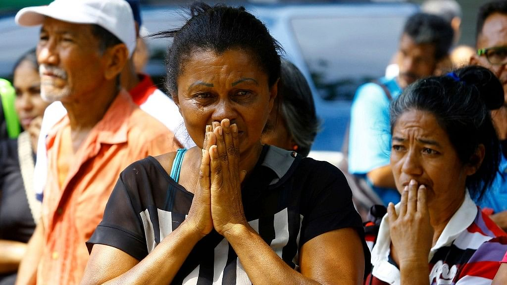 Relatives wait to hear news about the fate of detained prisoners at a police station where a riot broke out, in Valencia, Venezuela.