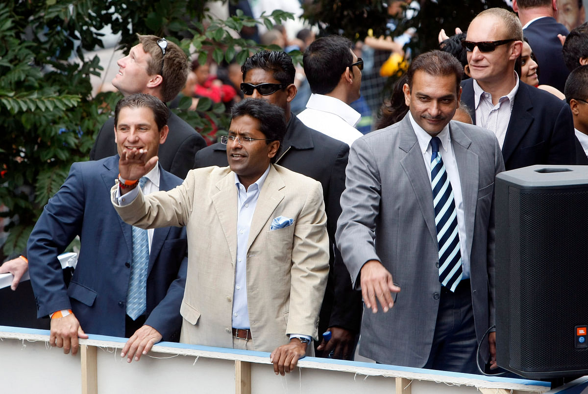 Chairman of the Indian Premier League (IPL) Lalit Modi (C) and and former cricketer Ravi Shastri (R) wave to crowds during a street parade by teams competing in the IPL in Cape Town in 2009.