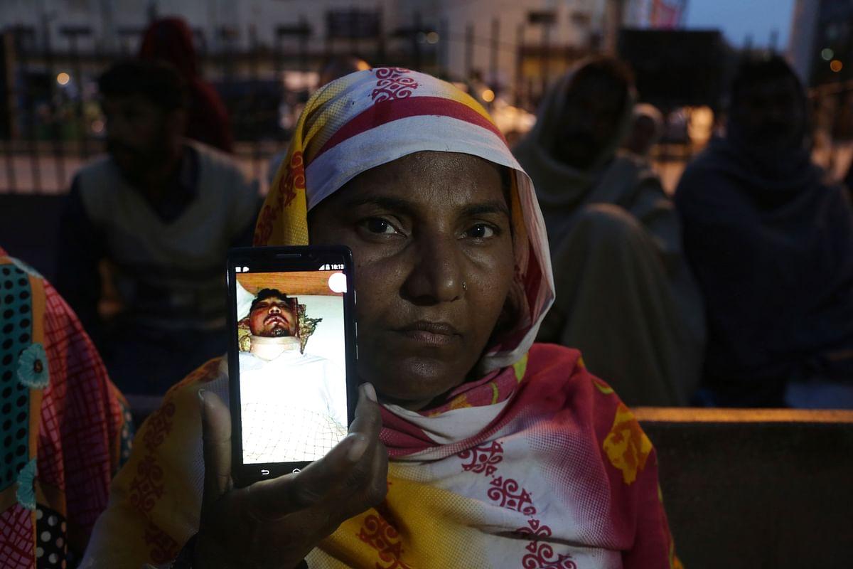 Nasreen Bibi shows picture of her injured son Sajid Masih, a blasphemy suspect
