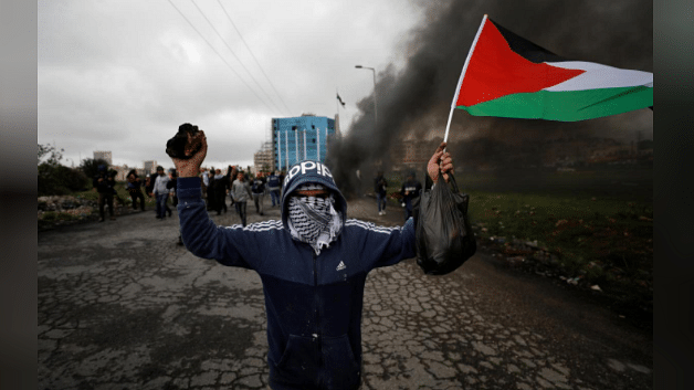 A demonstrator holds a Palestinian flag during clashes with Israeli troops.