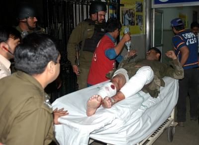 LAHORE (PAKISTAN), March 14, 2018 (Xinhua) -- People transfer an injured man to a hospital in Lahore, eastern Pakistan, on March 14, 2018. At least one person was killed and 20 others injured including several policemen on Wednesday evening in a blast in Pakistan