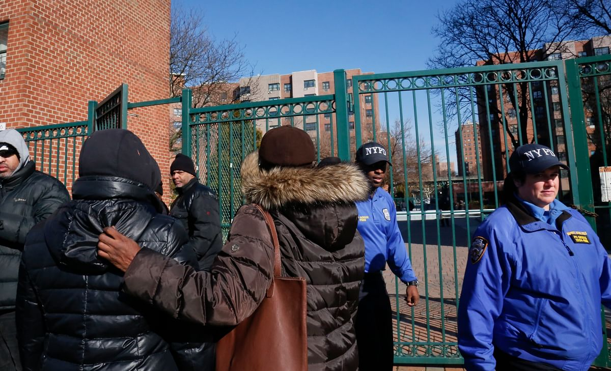 Neighbors gather outside the apartment in New York, where four people, including a young child, were found shot to death on 14 March.