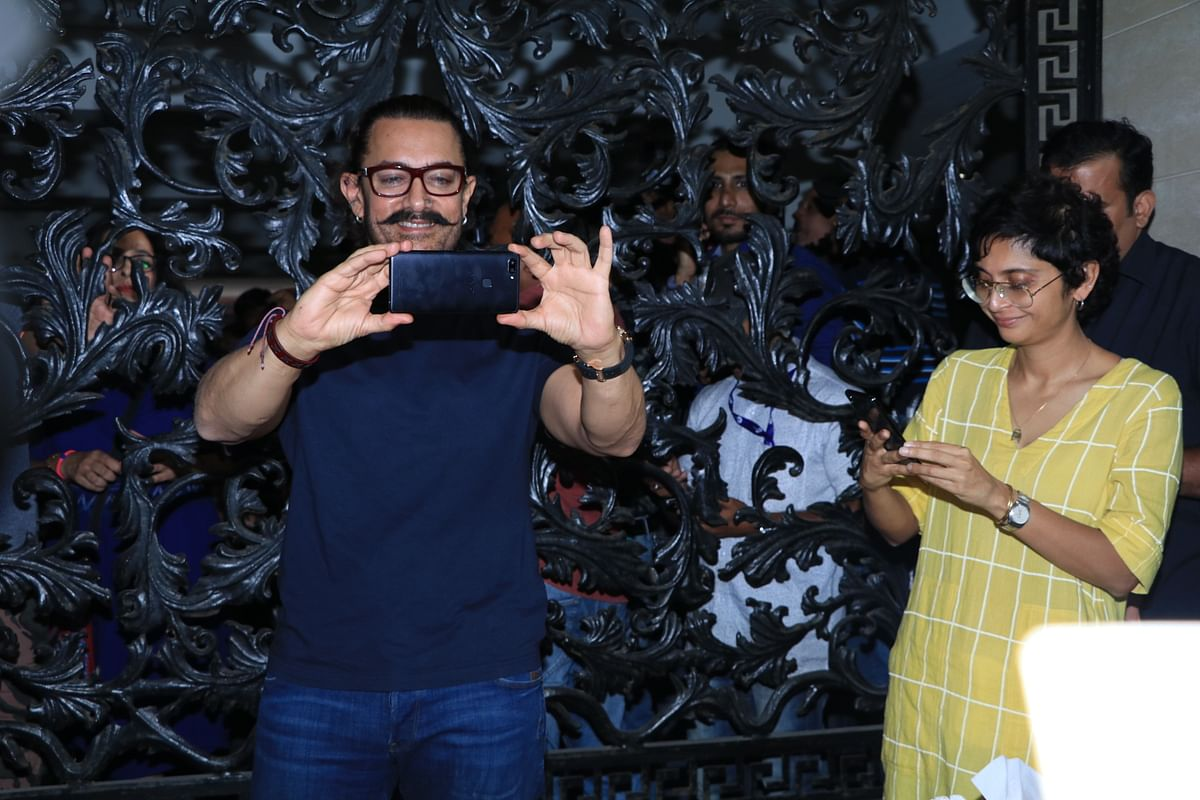 Aamir and Kiran take pictures of the celebration.