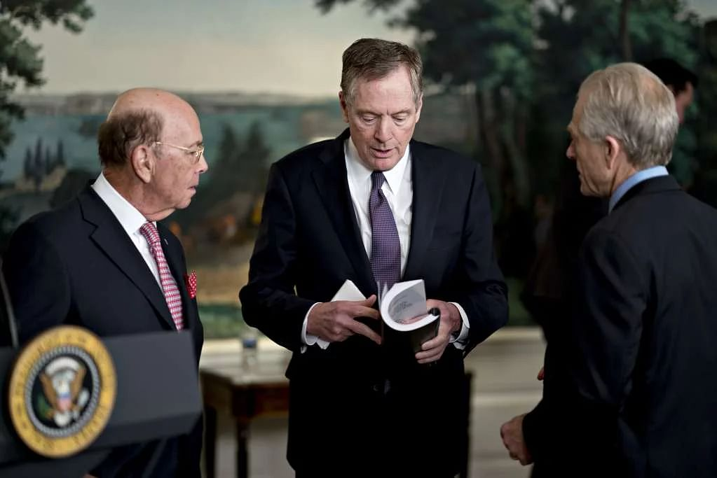 Peter Navarro, director of the National Trade Council, from right, Robert Lighthizer, US trade representative, and Wilbur Ross, US commerce secretary, speak before US President Donald Trump, not pictured, signs a presidential memorandum targeting China's economic aggression in the Diplomatic Room of the White House in Washington, DC, US, on 22 March 2018.
