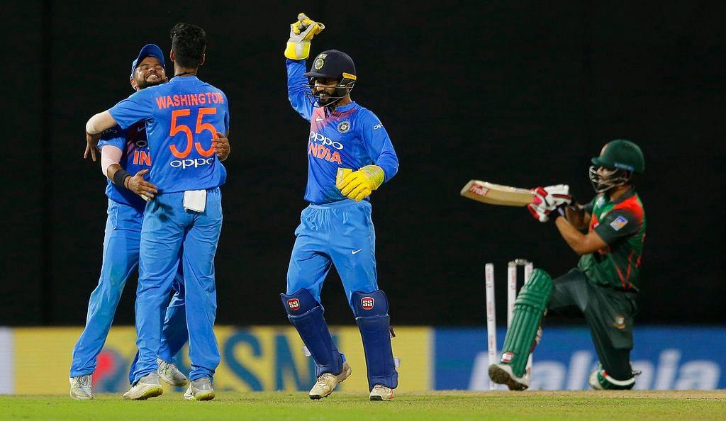 Washington Sundar celebrates a wicket with his teammates.