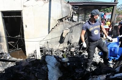 BULACAN PROVINCE, March 17, 2018 (Xinhua) -- A man works at the plane crash site in Bulacan Province, the Philippines, on March 17, 2018. Ten people were killed after a six-seater light plane crashed into a house in northern Philippines on Saturday, authorities said. (Xinhua/Stringer/IANS)