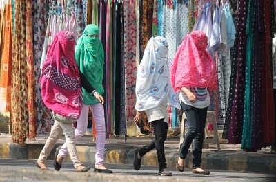Women cover their faces to avoid direct contact with sun on a hot day. (File Photo: IANS)