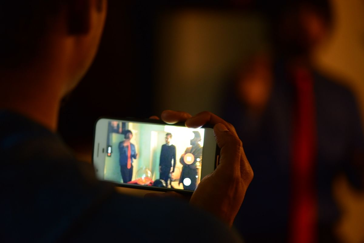 A member of audience taking a photograph of the immersive theatre production.