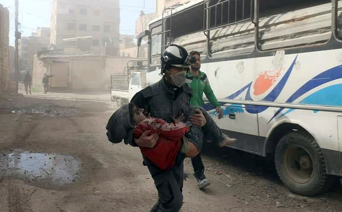 Syrian Civil Defense group carrying a boy who was wounded during airstrikes and shelling by Syrian government forces in Ghouta