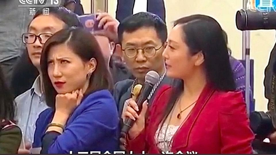 Picture of Liang Xiangyi rolling her eyes at her colleague Zhang Huijun of AMT.
