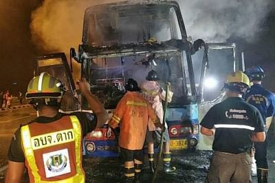 TAK : March 30, (Xinhua) Firefighters work at the site of a bus blaze in the northwestern Thai province of Tak, March 30, 2018. At least 20 Myanmar migrant workers were killed and three others wounded in a blaze on a bus in the northwestern Thai province of Tak in the wee hours on Friday, Thailand