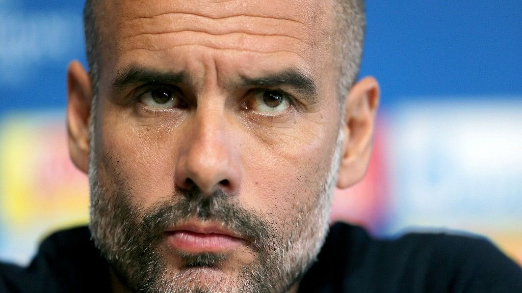 Manchester City coach Pep Guardiola listens to reporters' questions during a press conference in Manchester.