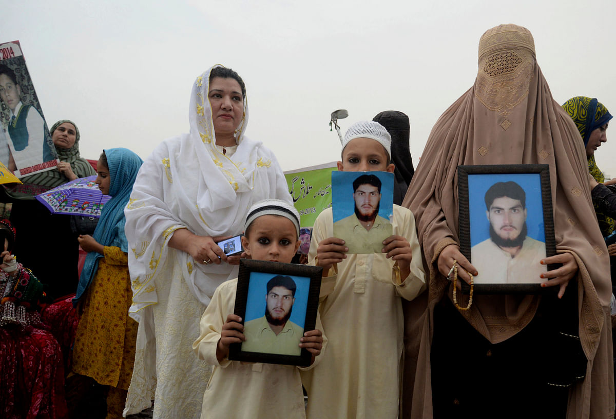 In this Sunday, 8 April 2018 file photo, a Pashtun family from a Pakistani tribal area display pictures of a missing family member during a Pashtun Protection Movement rally in Peshawar, Pakistan