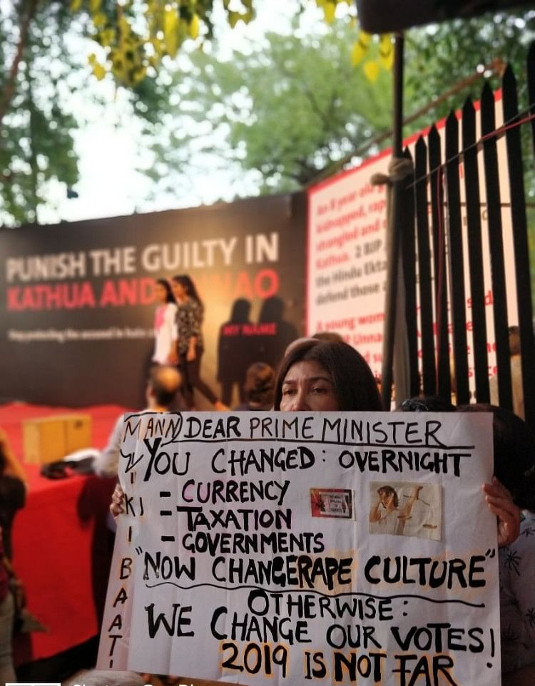 """A woman holding a placard asking the PM to take action and change the """"rape culture."""""""