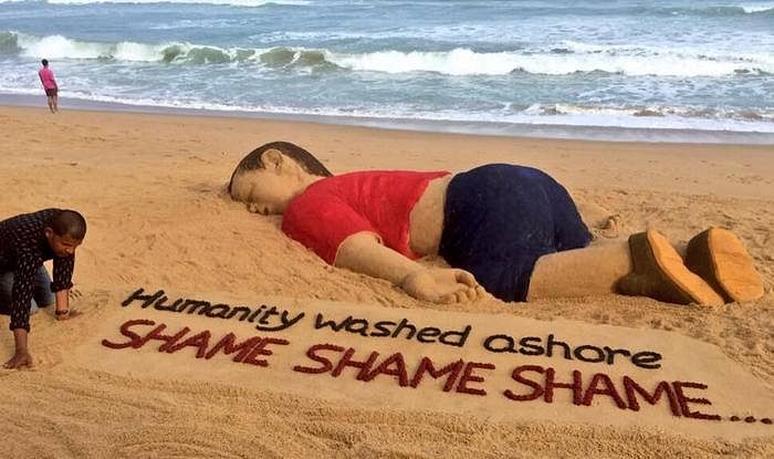 Sand artist Sudarsan Pattnaik works on a sculpture depicting Aylan Kurdi, who reportedly drowned in 2015 as his family tried to cross the Mediterranean Sea to flee Syria.