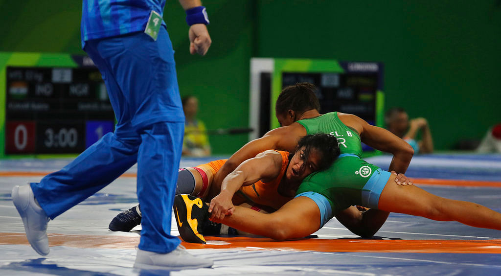 India's Babita Kumari, center, wrestles against Nigeria's Bose Samuel.