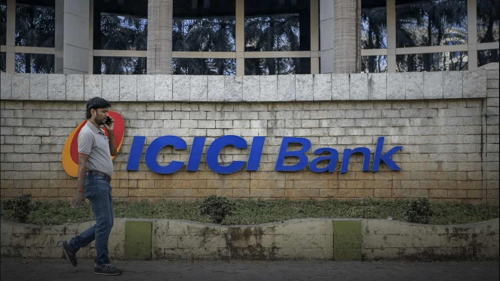 A man walking past an  ICICI Bank branch.