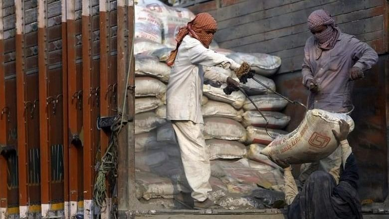 Workers unload cement bags from a truck near a construction site in New Delhi, India. Image used for representation.