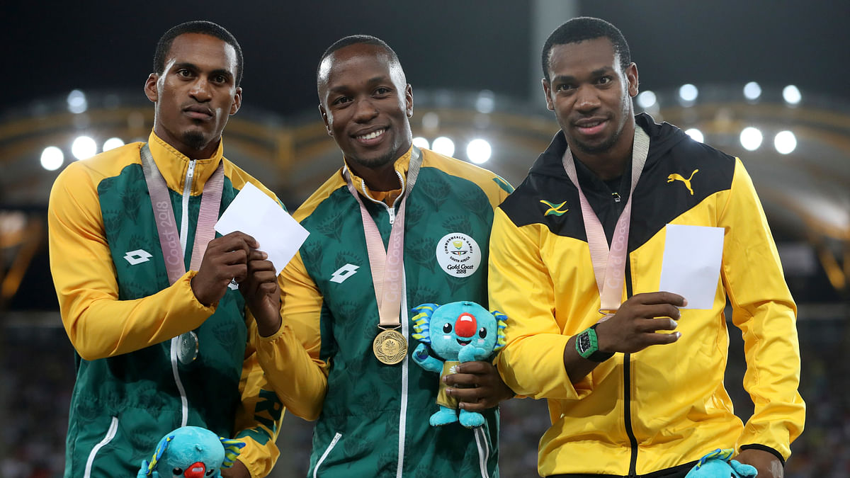 Men's 100m gold medalist South Africa's Akani Simbine, centre, stands with compatriot and silver medalist Henricho Bruintjies, left, and bronze medalist Jamaica's Yohan Blake, right, on the podium at Carrara Stadium during the 2018 Commonwealth Games on the Gold Coast, Australia, Tuesday, April 10, 2018.