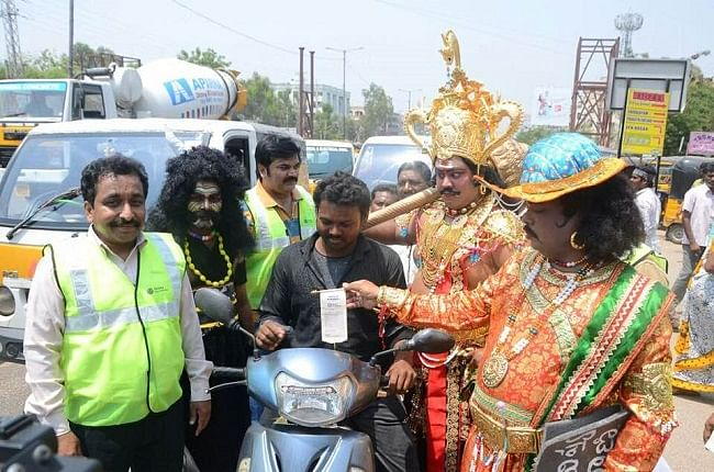 Actor playing Chitragupta hands over a receipt of a fine levied to a commuter