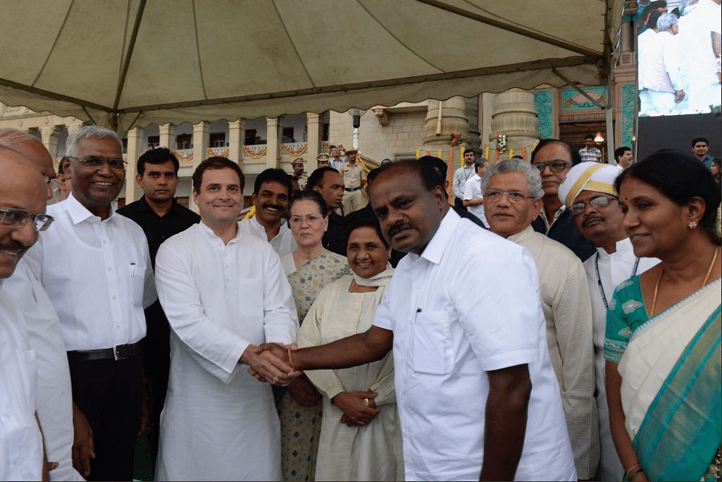 Rahul Gandhi clasps hands with new Karnataka Chief Minister HD Kumaraswamy.