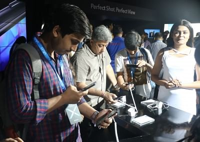 New Delhi: People check out the features of newly launched Vivo X21 smartphone, during its launch programme in New Delhi on May 29, 2018. (Photo: IANS)