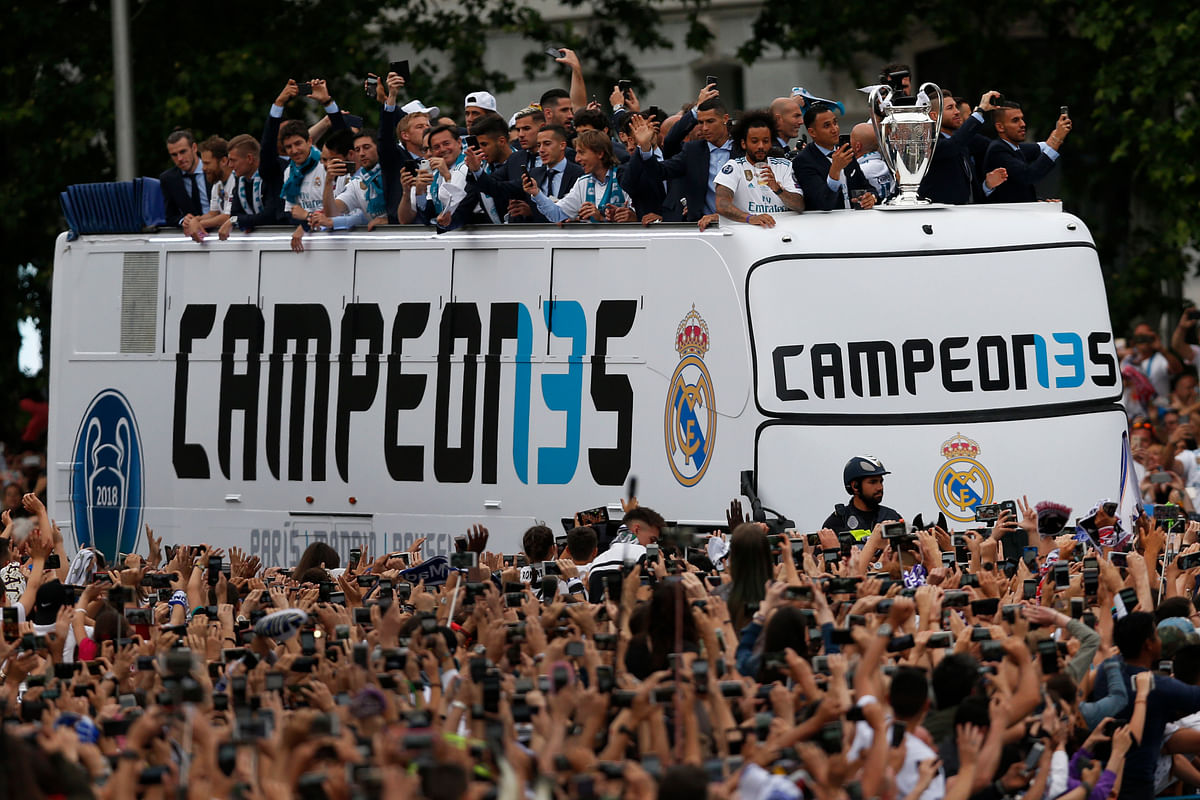 Real Madrid players wave to fans from the top of an open top bus in Cibeles square in Madrid.