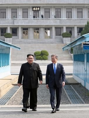 Panmunjom: South Korean President Moon Jae-in (R) and North Korean leader Kim Jong-un head to a summit site at the truce village of Panmunjom on April 27, 2018.(Yonhap/IANS)
