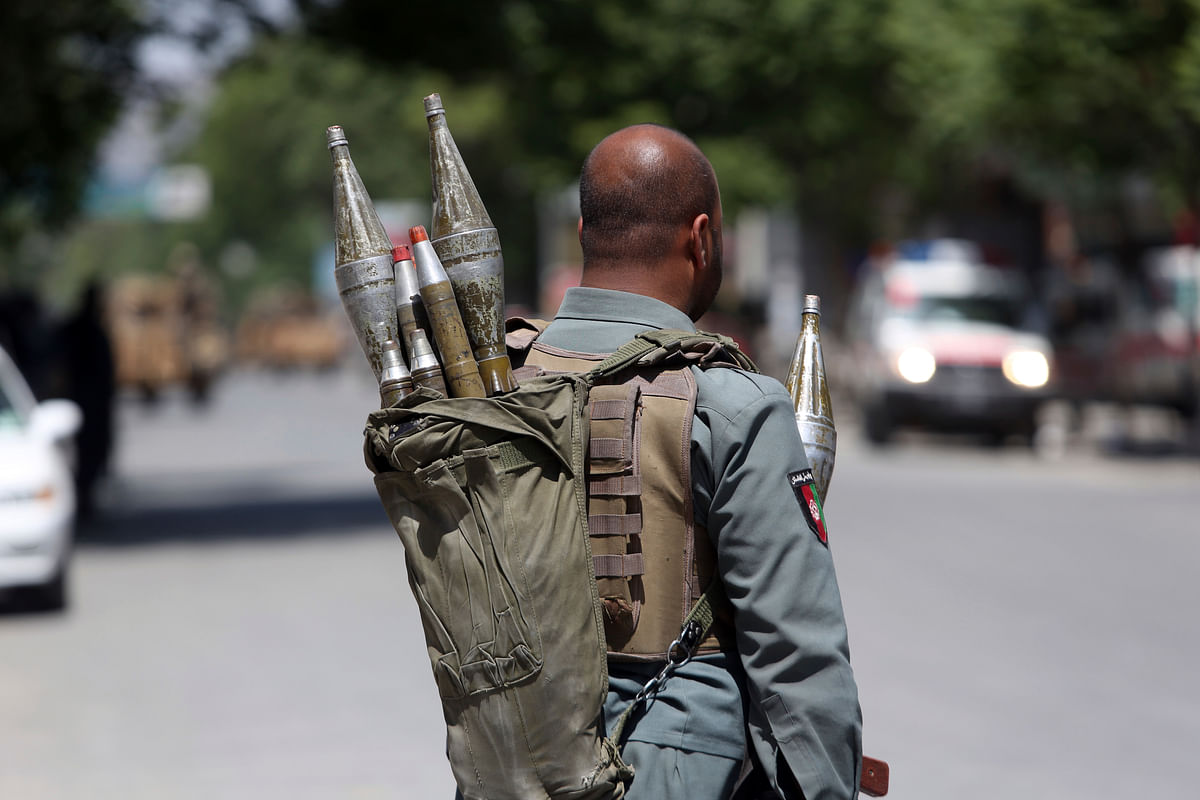 An Afghan security personnel stands at the site of a suicide attack, in the center of Kabul, Afghanistan.