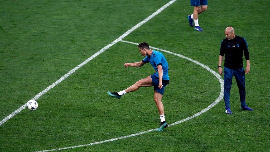 Real Madrid coach Zinedine Zidane watches as Cristiano Ronaldo kicks the ball during a training session at the Olimpiyskiy Stadium in Kiev in Ukraine, Friday,