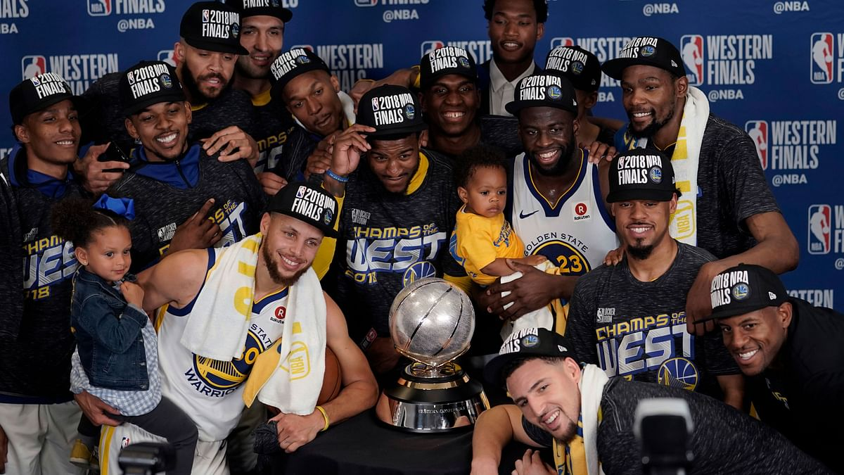 The Golden State Warriors pose with their trophy after defeating the Houston Rockets in Game 7 of the NBA basketball Western Conference finals, Monday, May 28, 2018.