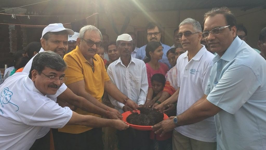 CAG Rajiv Mehrishi (in yellow) emptied out a twin-pit toilet in rural Maharashtra in a bid to break sanitation taboos.