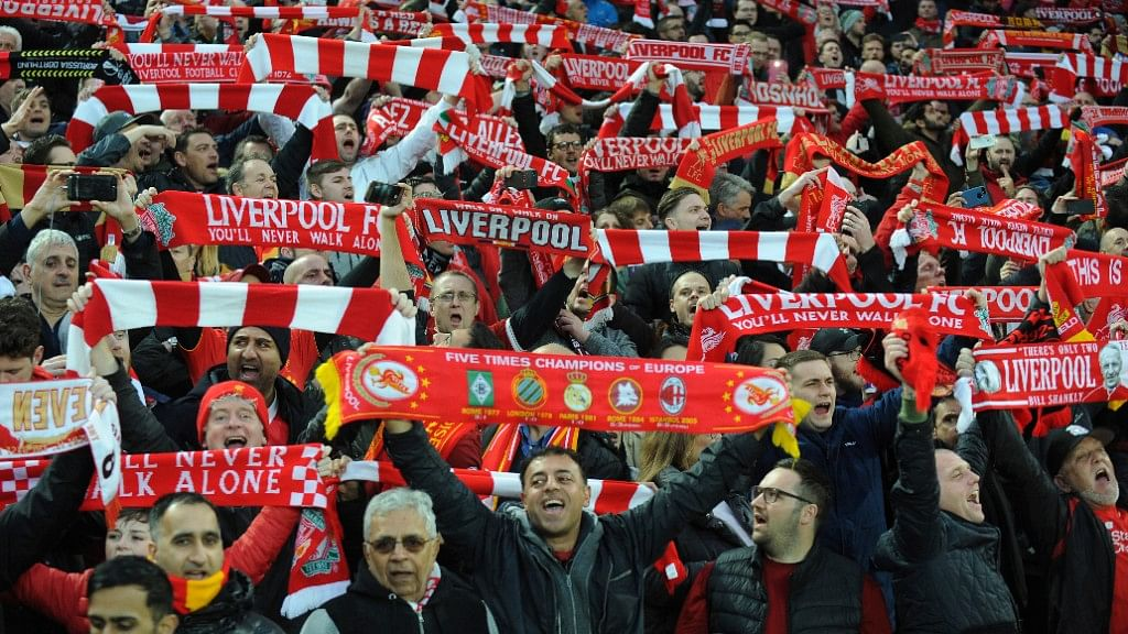 """Liverpool fans sing """"You'll Never Walk Alone"""" as they hold up scarves prior to the Champions League semi-final."""