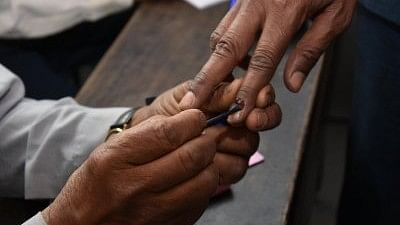 A polling official applies indelible phosphorus ink on the fore finger of a voter.