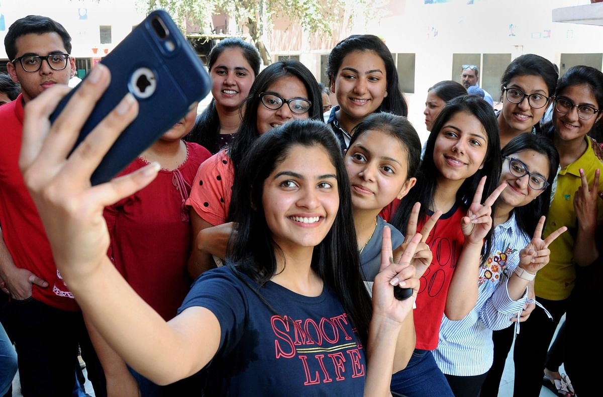 Students take selfies as they celebrate  at St. Thomas school in New Delhi on Saturday.