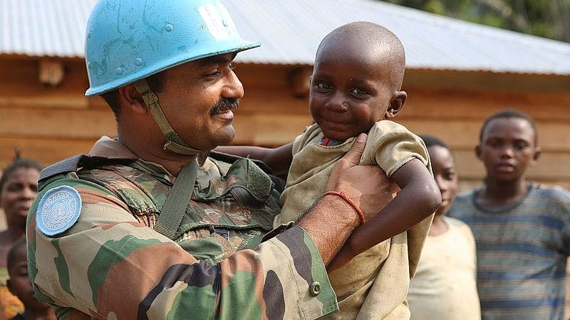 An Indian peacekeeper with a child in Congo.