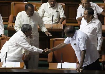 Bengaluru: Congress leader Siddaramaiah greets Karnataka Chief Minister H.D.Kumaraswamy at the state assembly in Bengaluru on May 25, 2018. (Photo: IANS)