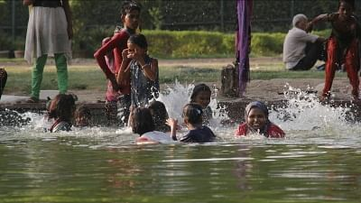 New Delhi: Children enjoy inside a water pond at India Gate to get respite from the heat on a hot sunny day, in New Delhi on May 26, 2018. (Photo: IANS)