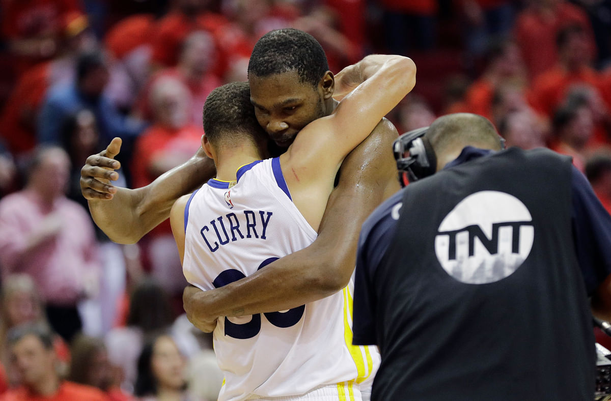 Golden State Warriors forward Kevin Durant, right, hugs teammate Stephen Curry, left, after they defeated the Houston Rockets in Game 7 of the NBA basketball Western Conference finals, Monday, May 28, 2018, in Houston.