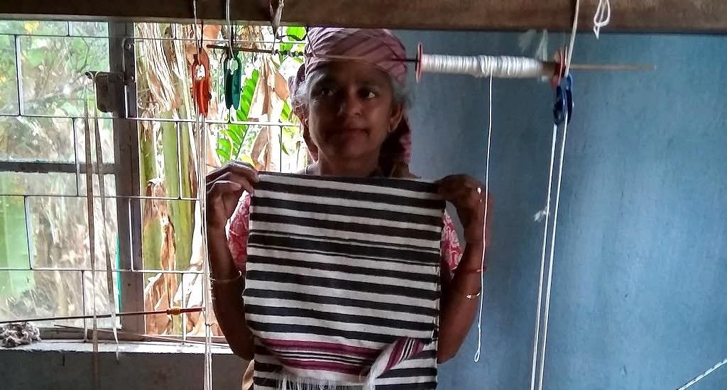 A Bhoi woman displays a just woven stole in the Diwon workshop.