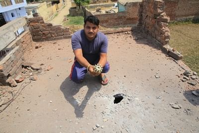 Jammu: A man shows a part of a mortar shell, in Jammu on May 22, 2018. The Pakistani Rangers on Tuesday continued shelling on the international border (IB) in the Jammu and Samba districts of Jammu and Kashmir affecting 30 BSF border outposts and some two dozen villages. Cattles have perished and houses have been damaged in the Pakistani ceasefire violation. (Photo: IANS)