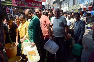 Shimla: Locals wait in a queue to collect drinking water from a tanker amid water crisis that hit many parts of the country during summers, in Shimla on May 26, 2018. (Photo: IANS)