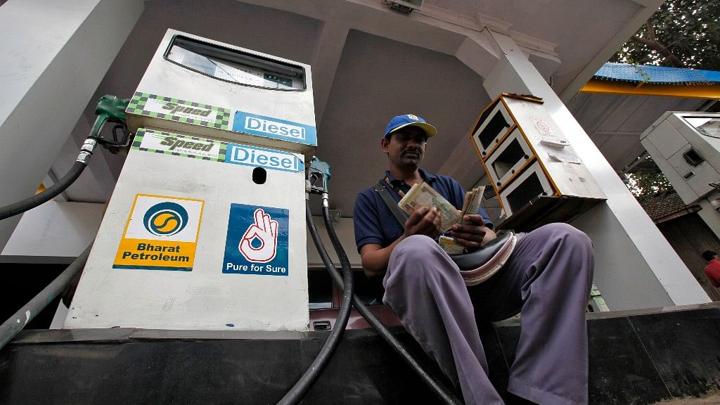 A petrol pump executive counts the cash collected from sales.