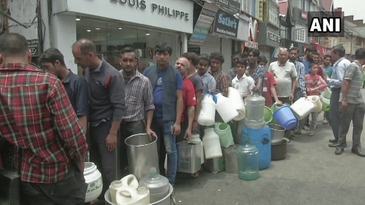 People stand in queues to fill water.