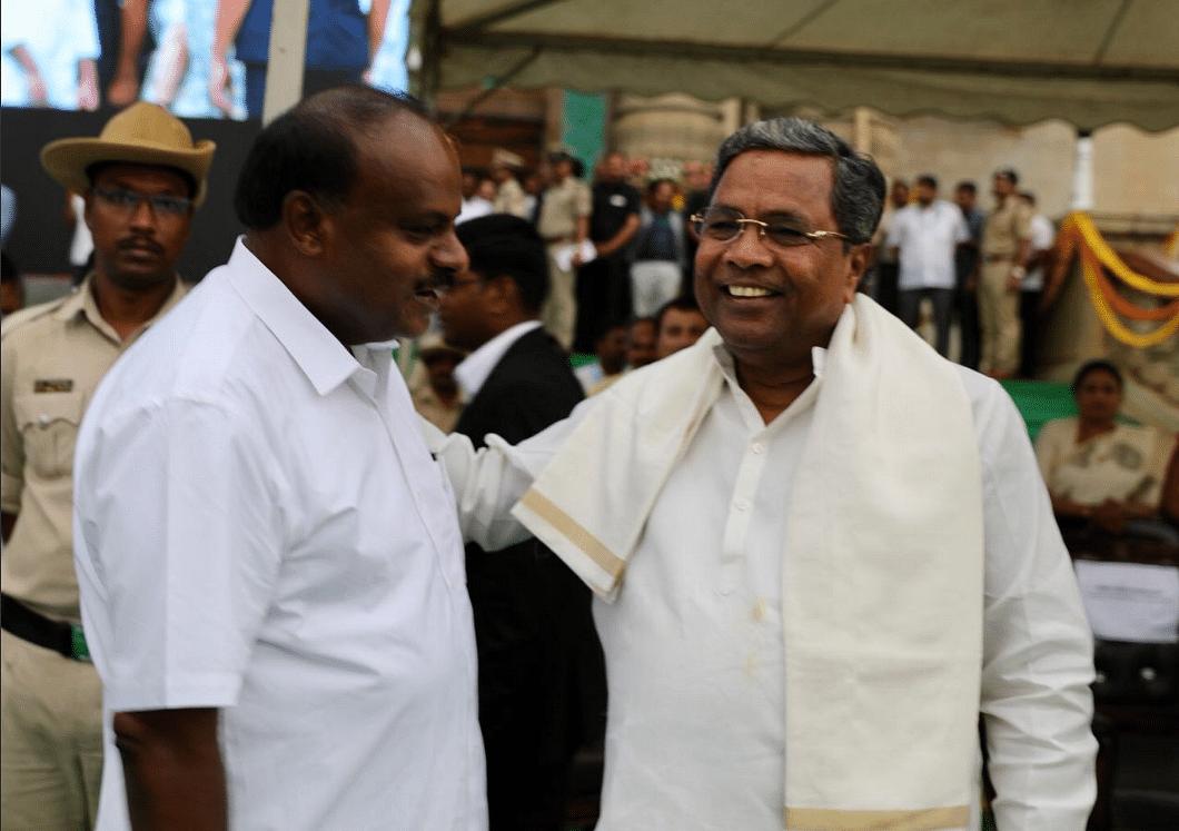 Siddaramaiah gives newly sworn-in Karnataka Chief Minister HD Kumaraswamy a friendly pat.