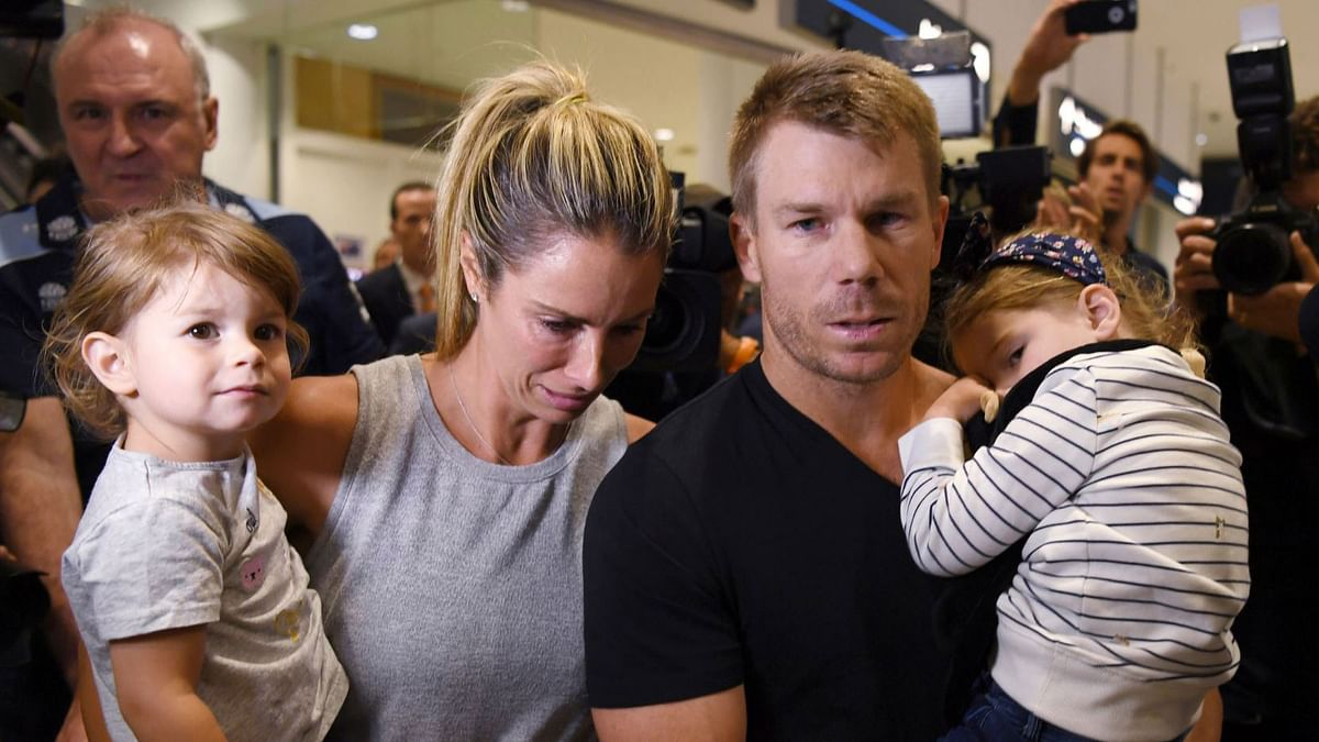 David Warner and his wife Candice at the Sydney airport with their daughters.